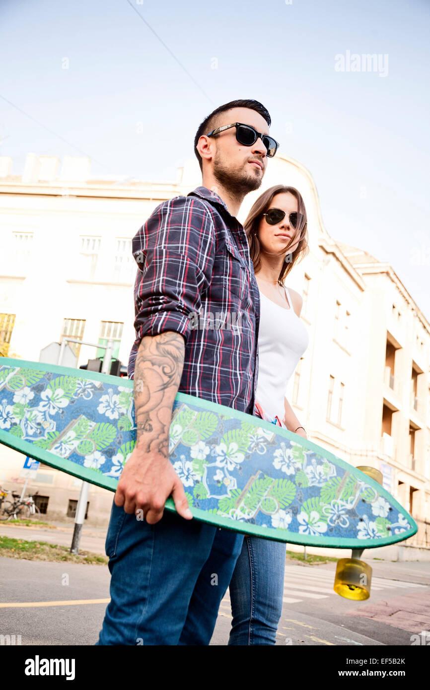 Junges Paar mit Skateboard zu Fuß in der Stadt Stockbild