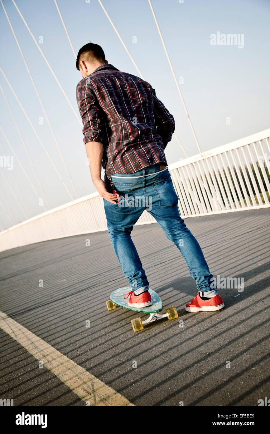 Junger Mann Skateboard über Brücke Stockbild