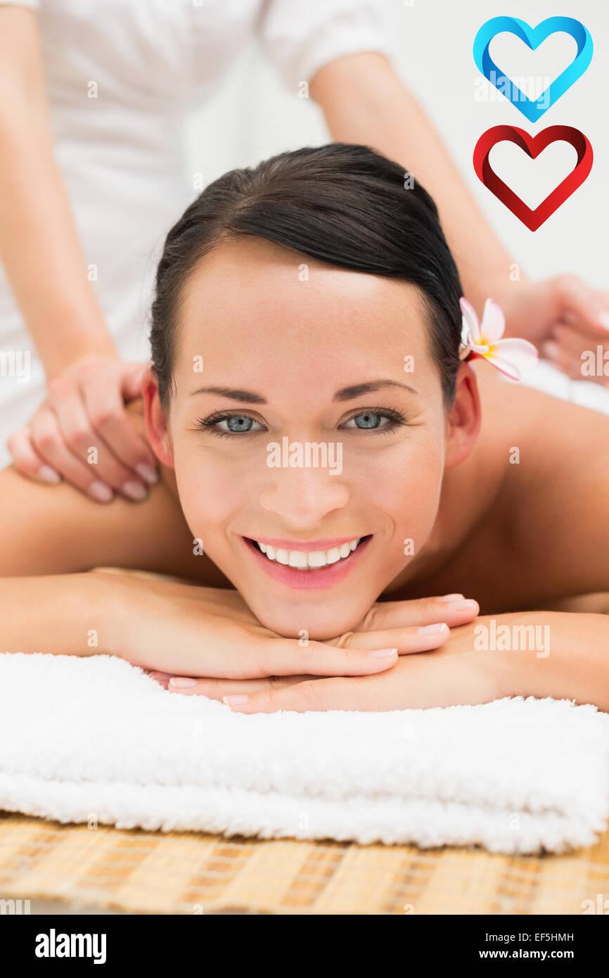 Zusammengesetztes Bild der friedlichen Brünette einer herbal Compress Massage lächelnd in die Kamera Stockbild