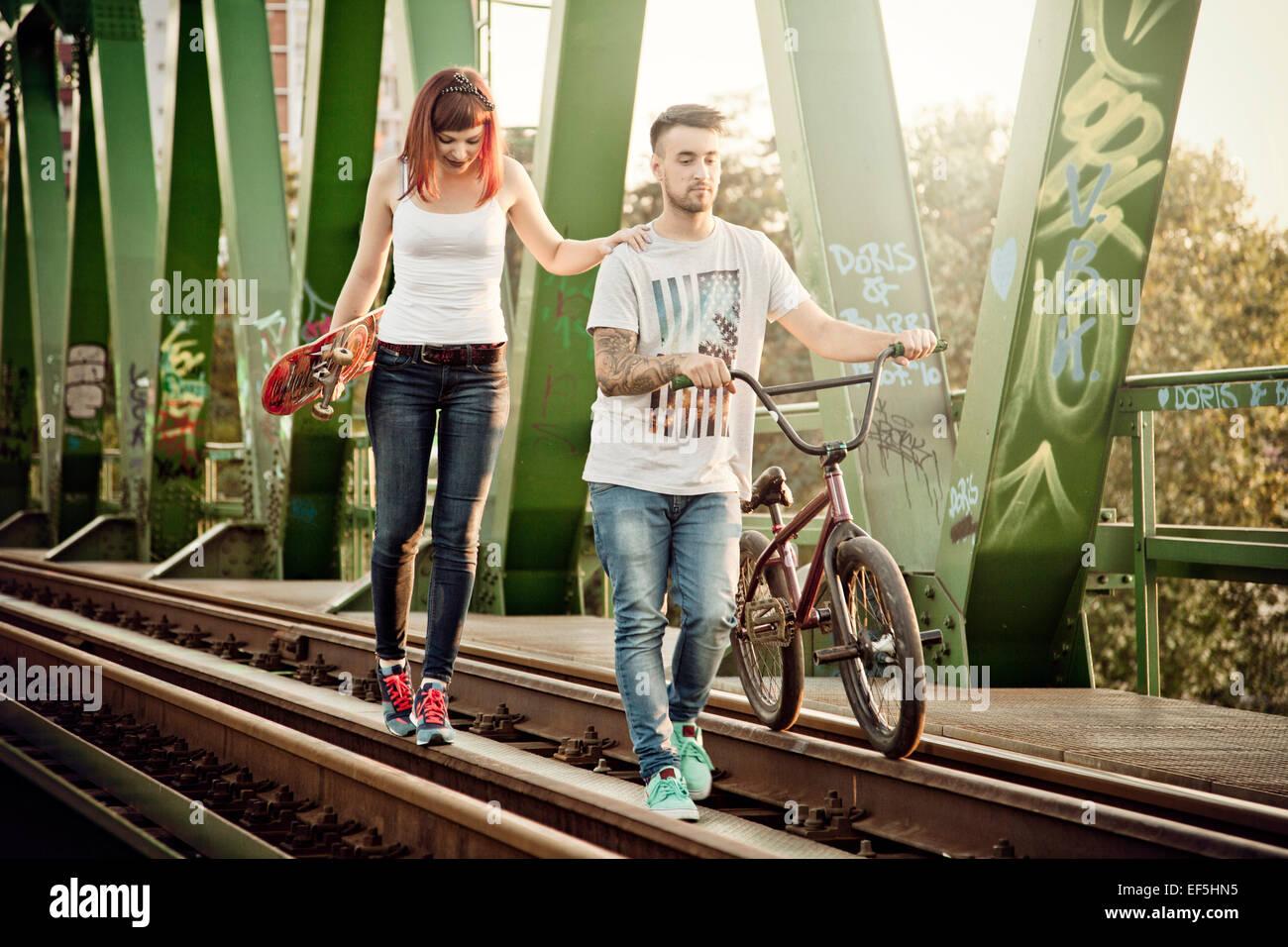 Junges Paar mit Skateboard und BMX Fahrrad im freien Stockfoto