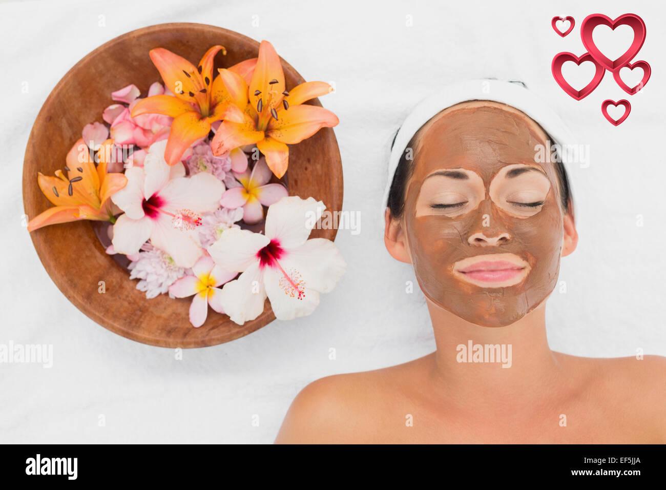 Zusammengesetztes Bild des lächelnden Brünette immer eine Schlammbehandlung Gesicht neben Schale mit Blumen Stockbild