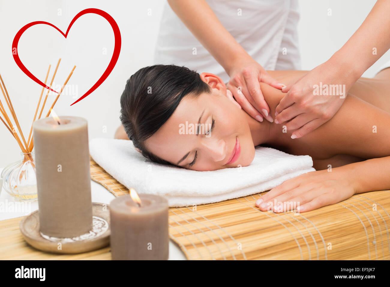 Zusammengesetztes Bild schöne Brünette einer Schulter Massage lächelnd in die Kamera Stockbild