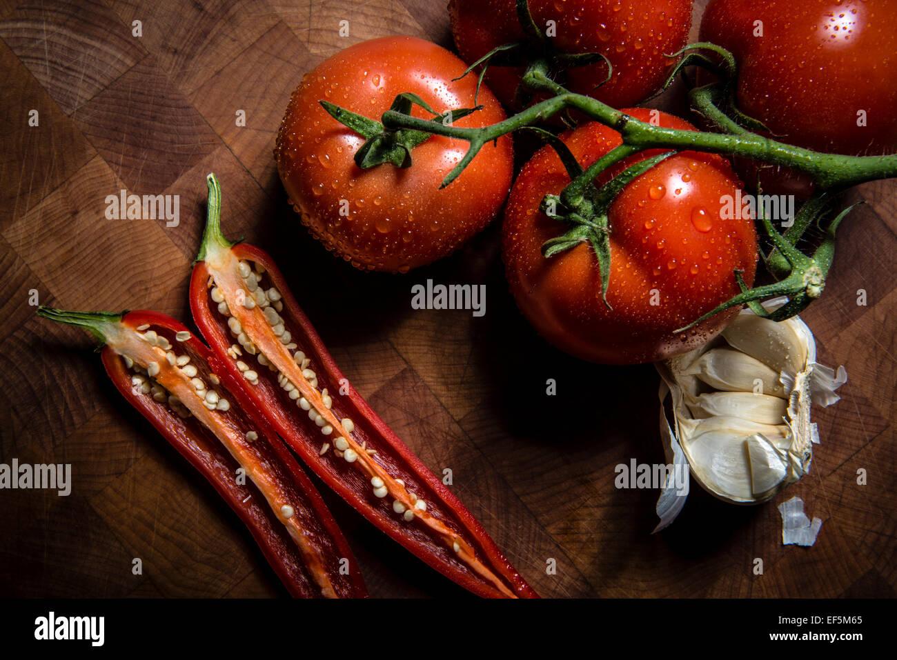 Tomaten, rote Chili und Knoblauch auf einem Schneidebrett Stockbild