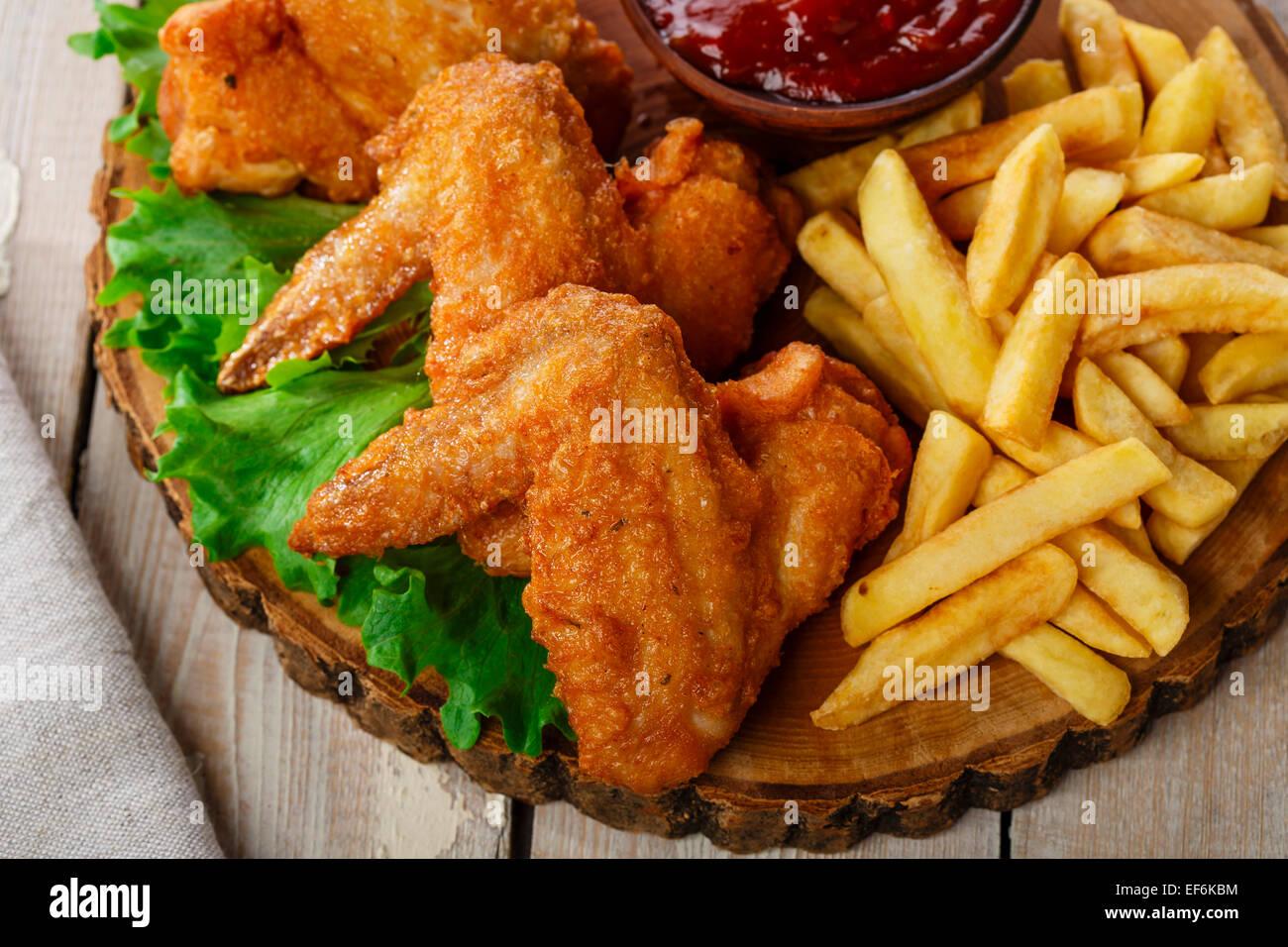 Gebratene Hähnchenflügel mit Sauce und Pommes frites Stockbild