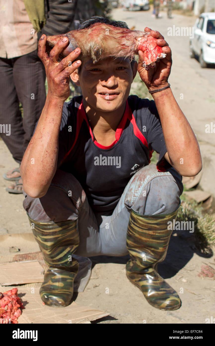 Junger Mann mit einer blutigen HUF ein Yak in den Straßen von einem kleinen Dorf-Markt in Arunachal Pradesh Stockbild