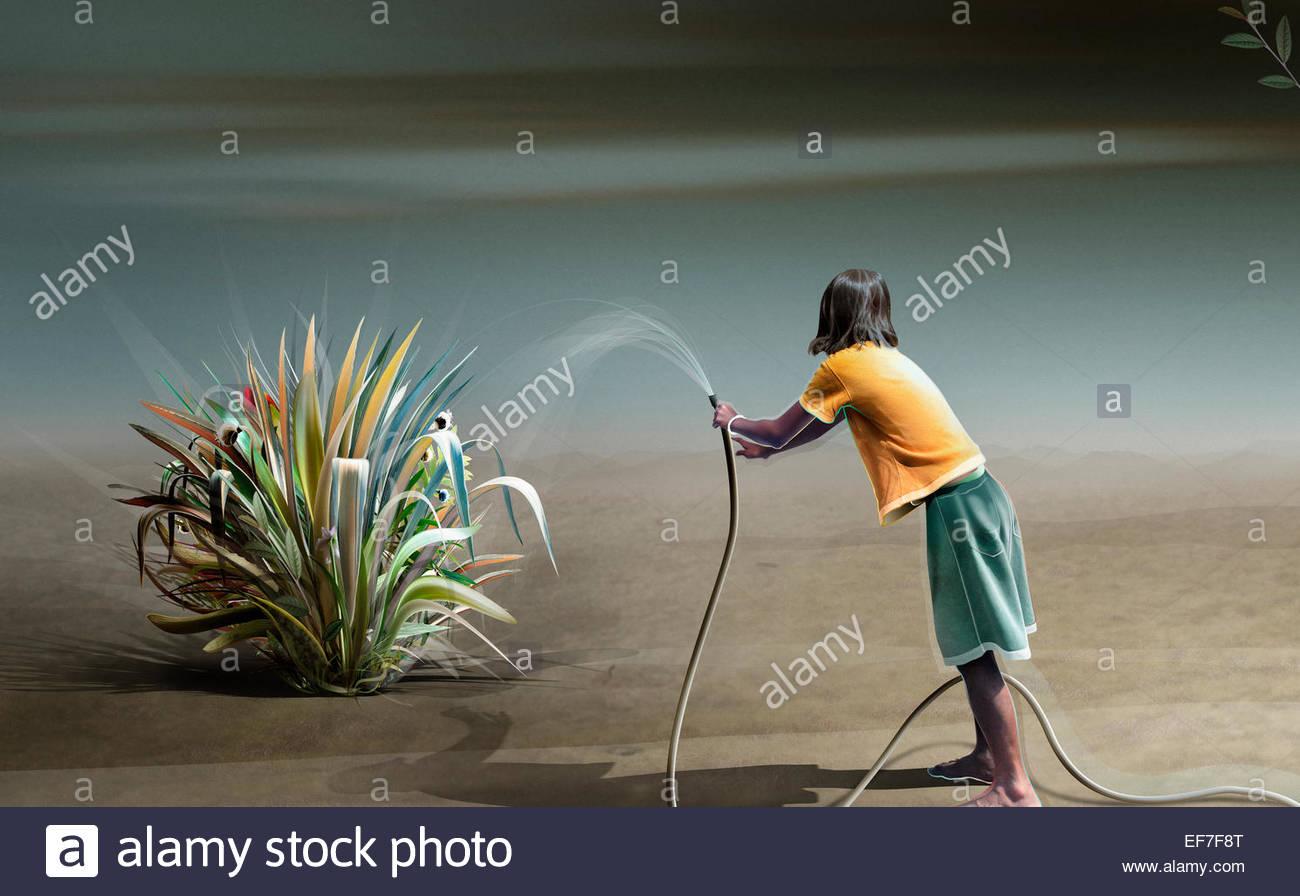 Teenager-Mädchen Bewässerung Anlage in der Wüste Stockbild