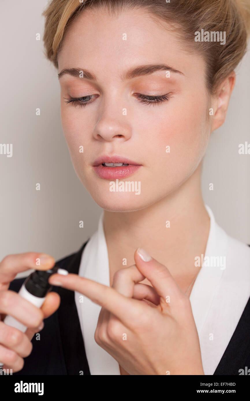 Frau Spritzen Feuchtigkeitscreme am finger Stockbild