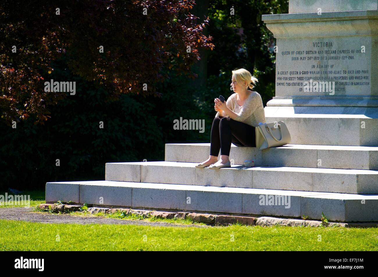 Frau hören ihre Musik auf einem Smartphone während der Standortwahl auf den Stufen eines Denkmals. Stockbild