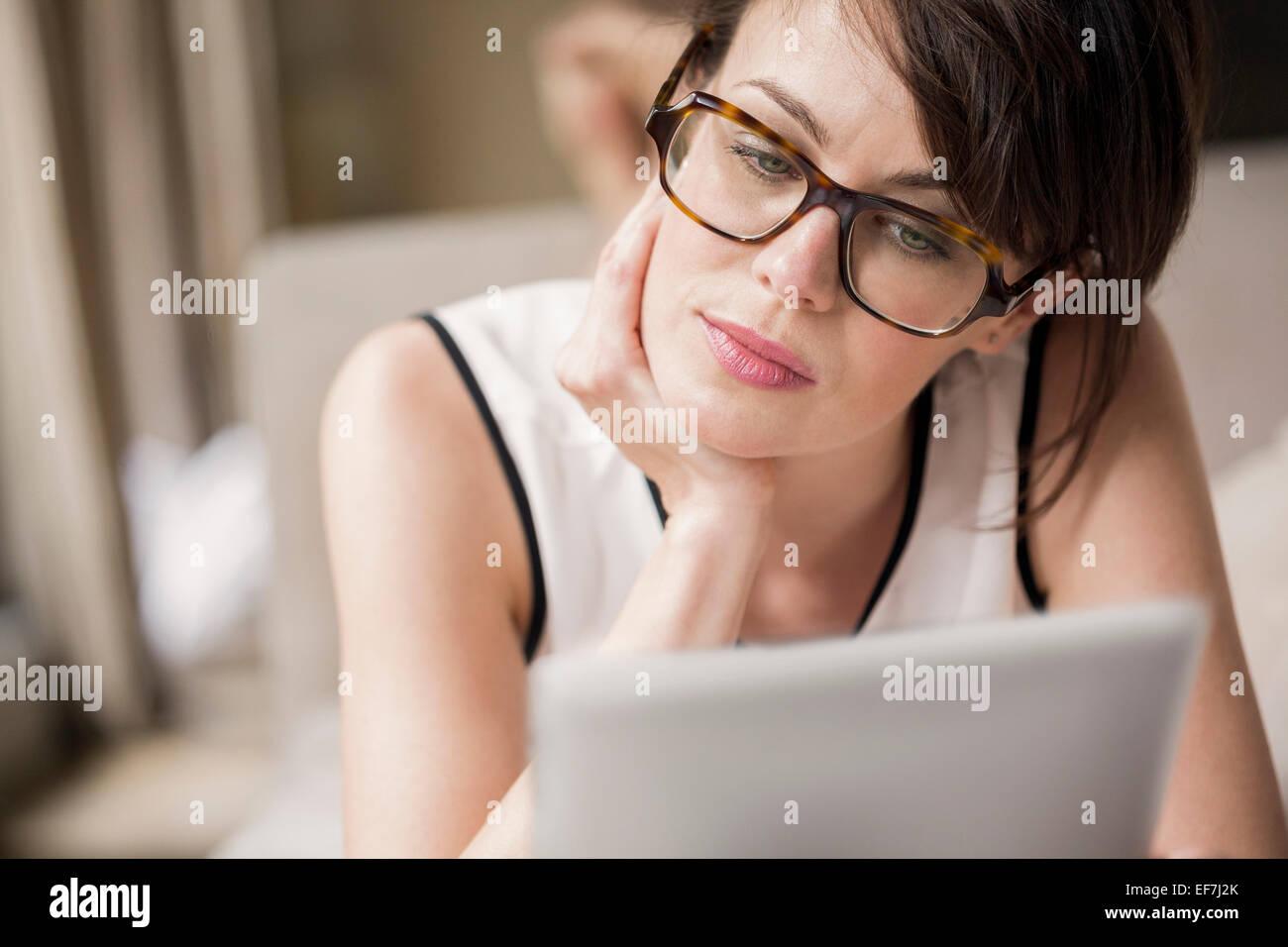Frau auf dem Bett liegend und mit Blick auf eine digital-Tablette Stockbild