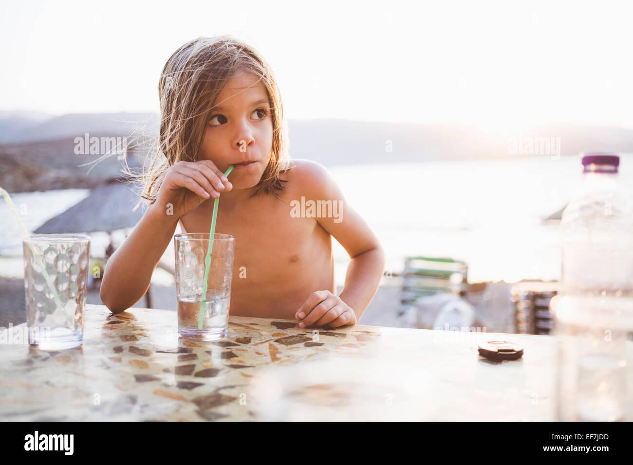 Junge mit Drink am Seeufer Stockbild
