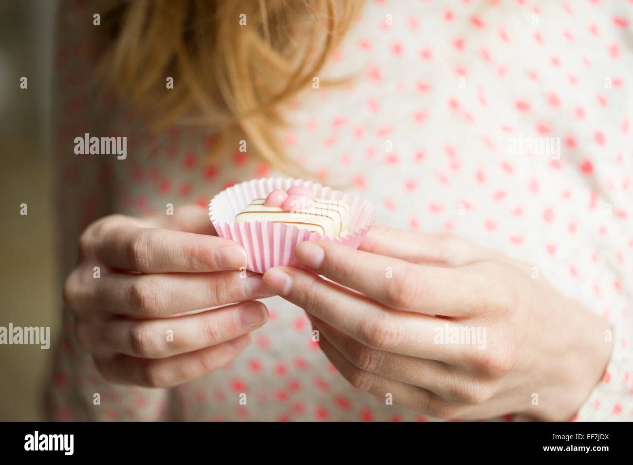 Frau einen Cupcake Essen Stockbild