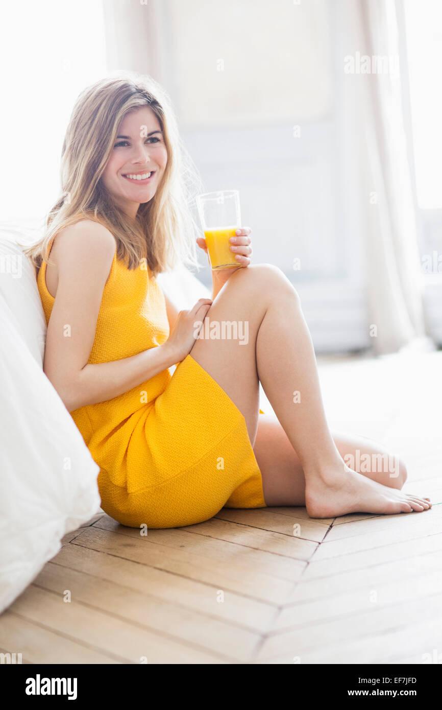 Frau trinkt Orangensaft Stockbild