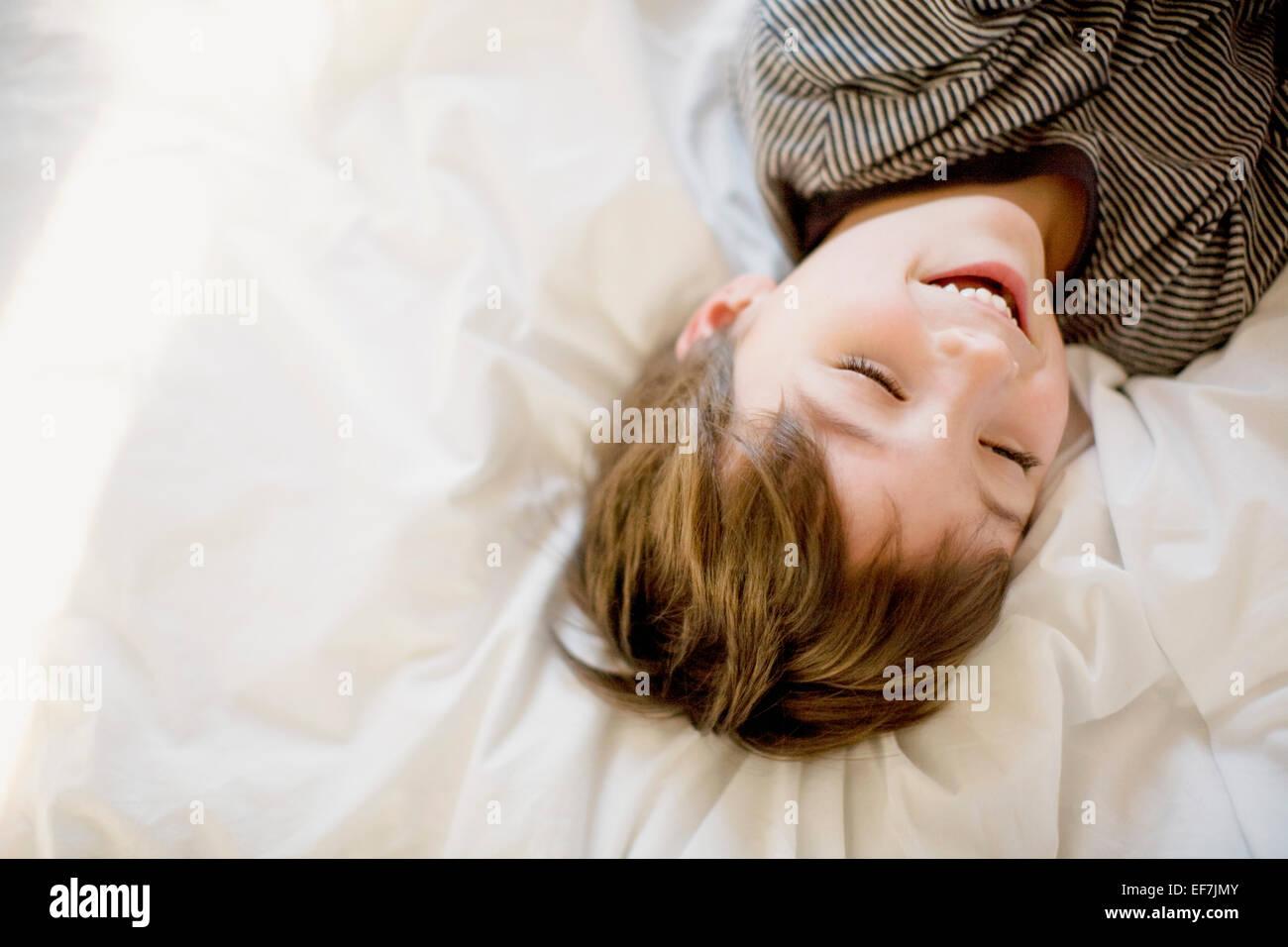 Fröhlicher Junge auf dem Bett liegend Stockbild