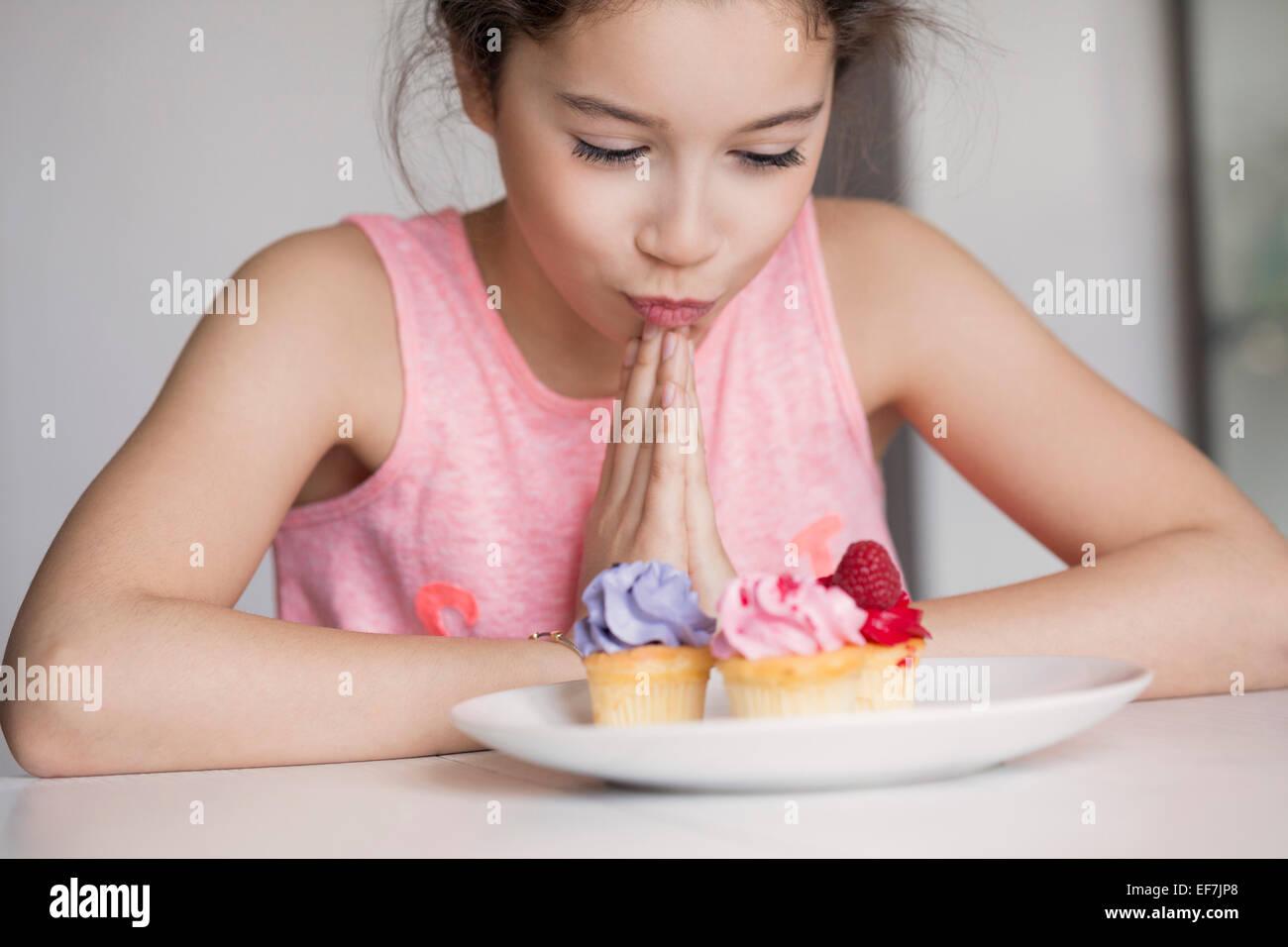 Mädchen auf der Suche bei cupcakes Stockfoto