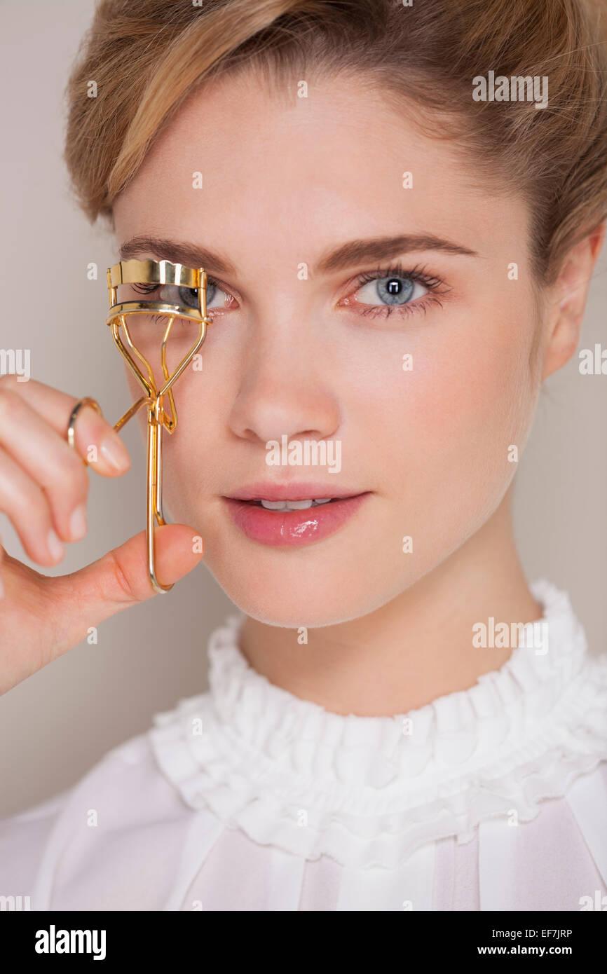 Schöne Frau, die ihre Wimpern mit einem Lockenwickler Eisstockschießen Stockbild