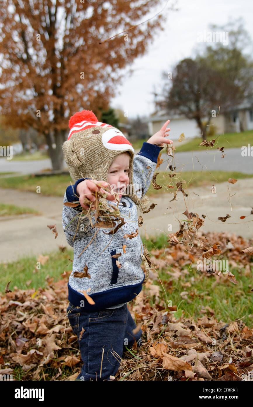 Jungen spielen mit Herbstlaub Stockbild