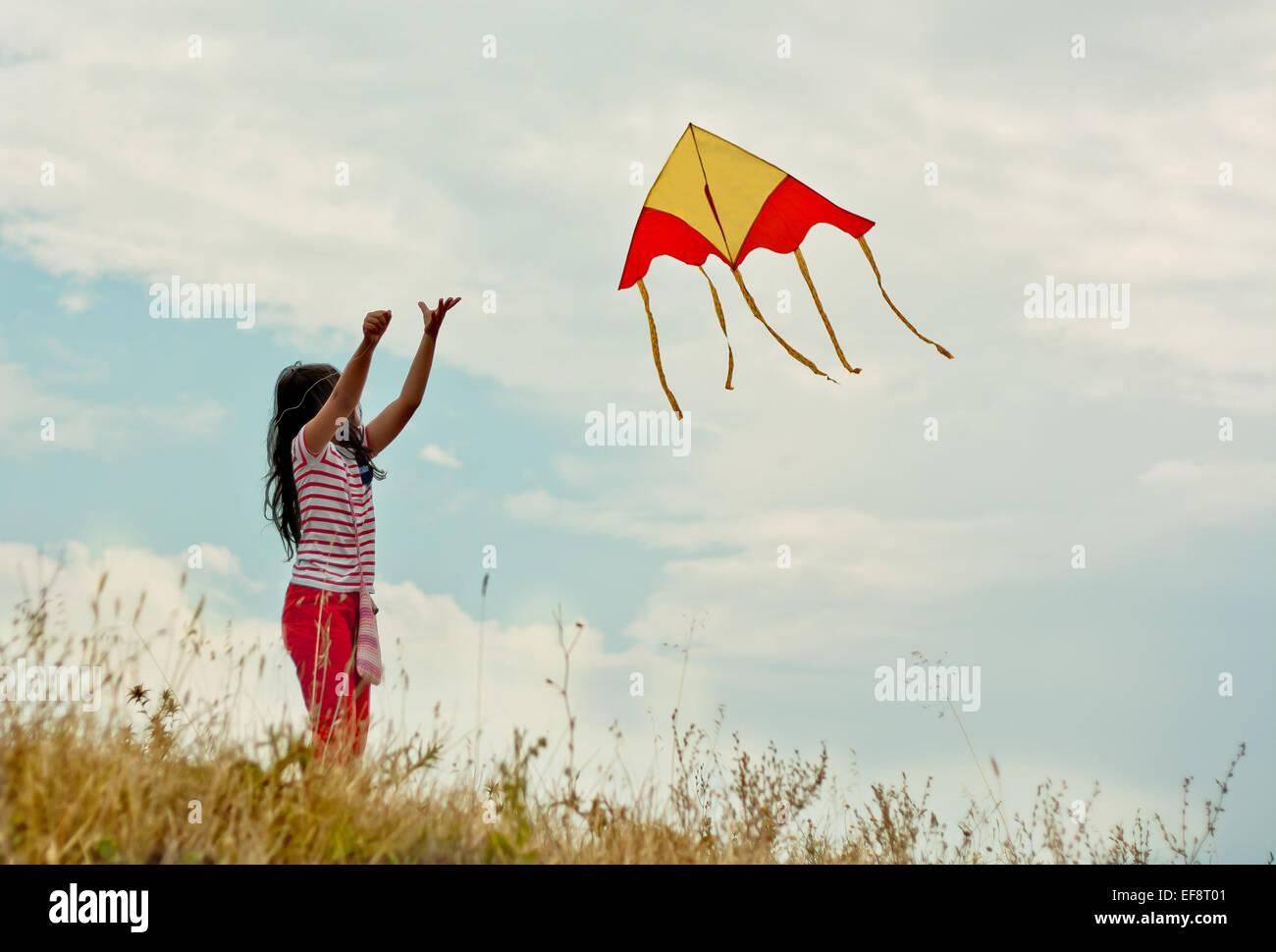Porträt eines Mädchens (8-9) fliegende Drachen auf Hügel Stockbild