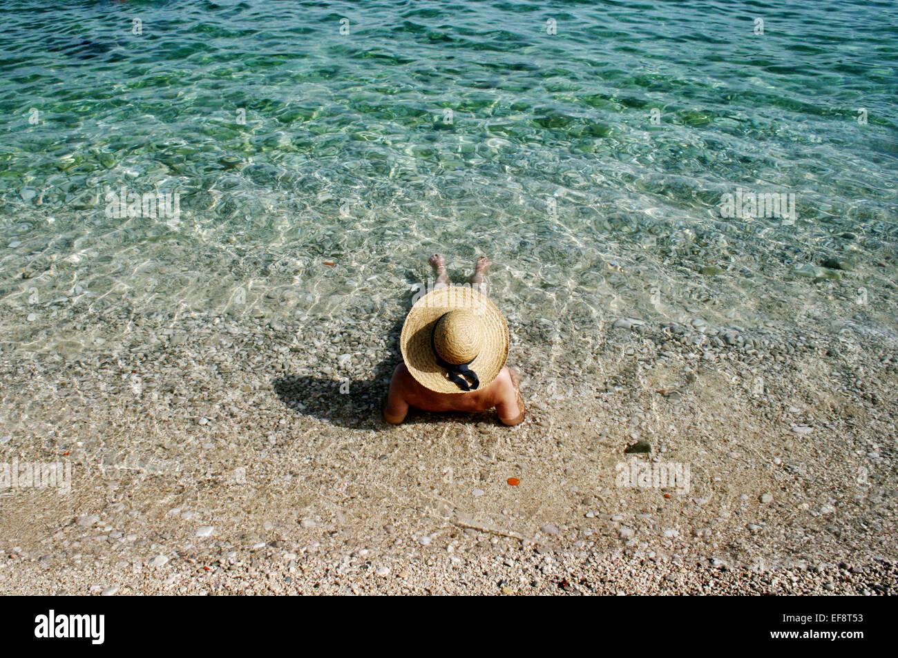 Kroatien, Frau mit Strohhut Sonnenbaden Stockbild