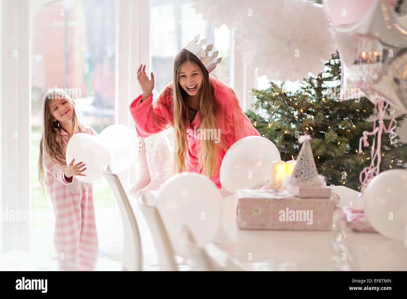 Zwei Mädchen (4-5,14-15) spielen mit Ballons Weihnachtsbaum Stockbild