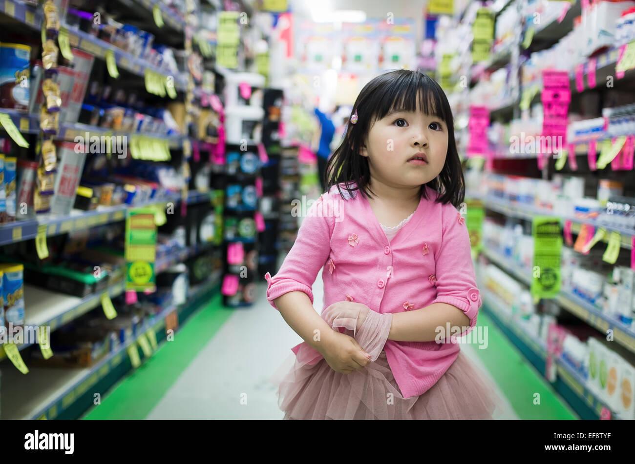 Vorderansicht des kleinen Mädchens allein zu Fuß zwischen den Ständen im Supermarkt Stockbild