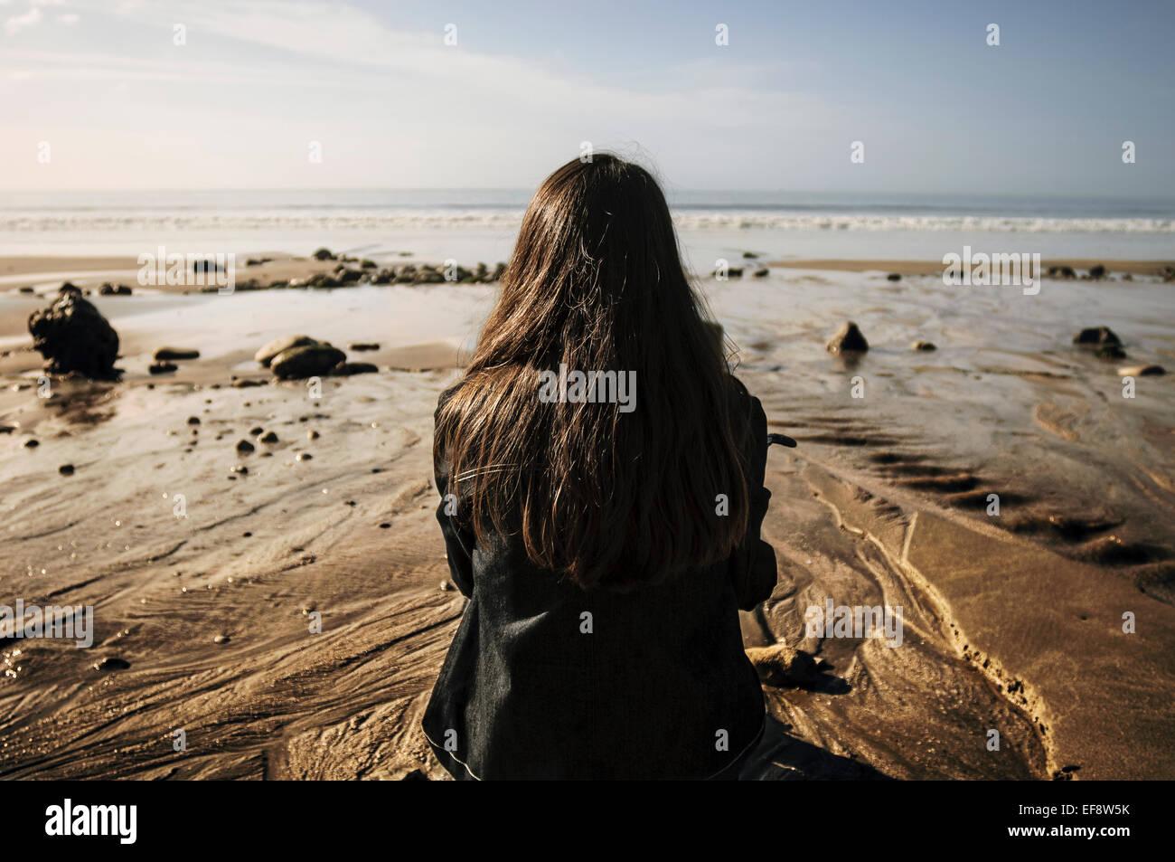 Frankreich, junge Frau sitzt auf Sand, Blick auf See Stockbild