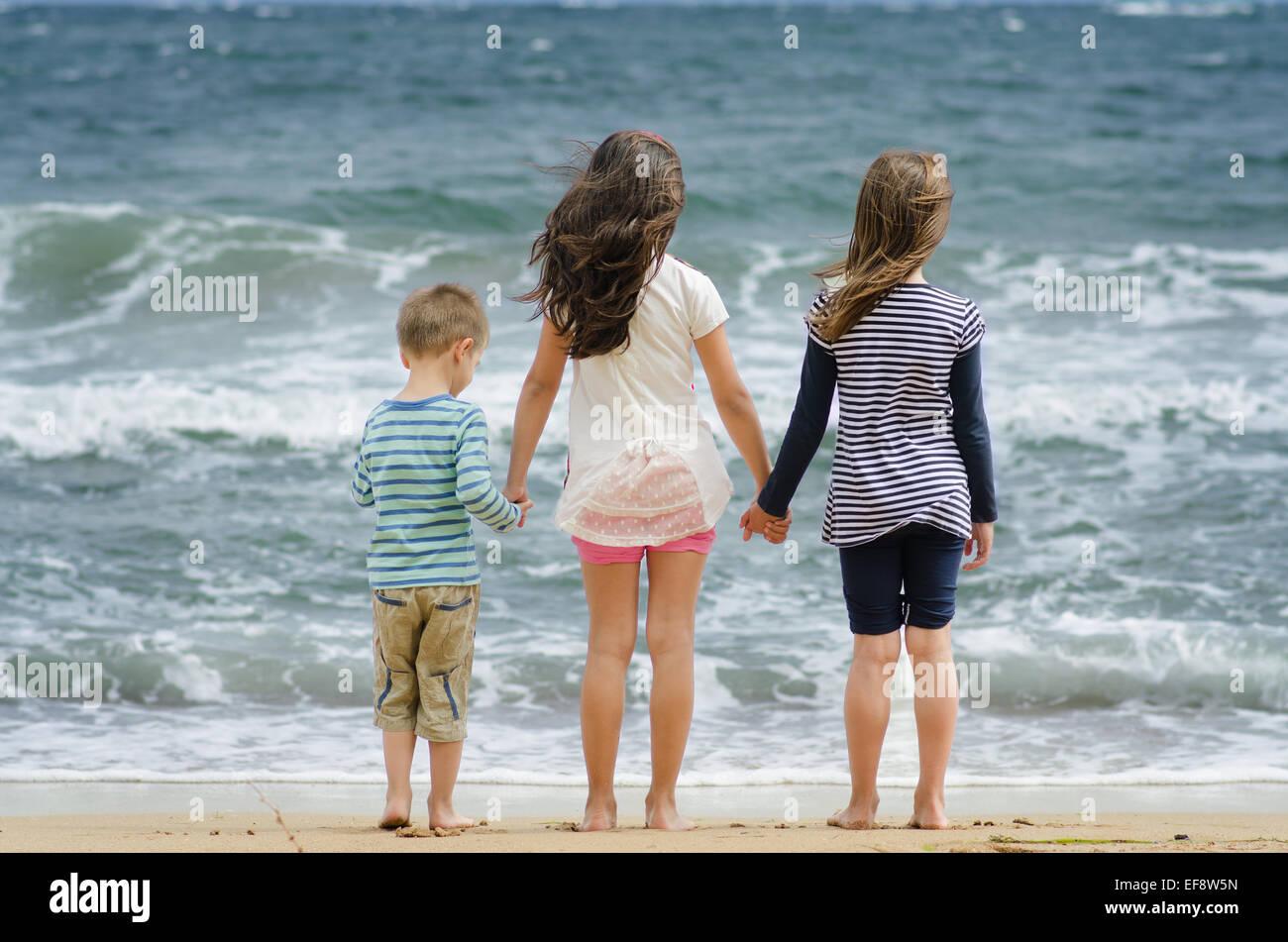 Bulgarien, zwei Mädchen (8-9) und junge (4-5) Stand am Surf Line Hand in Hand mit Blick auf Meer Stockbild
