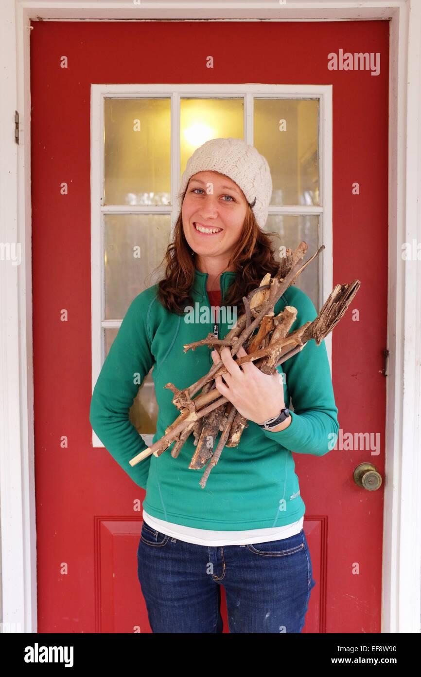 Junge Frau sammeln von Brennholz Stockbild