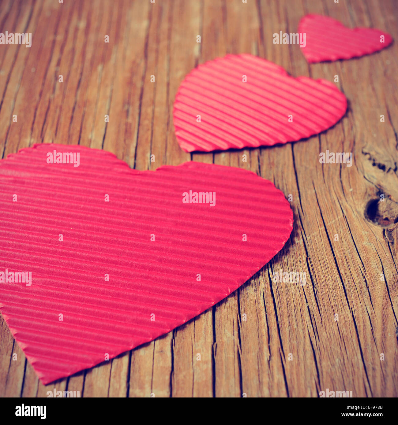 einige roten Herzen in verschiedenen Größen auf einer rustikalen Holzoberfläche mit einem Filtereffekt Stockbild