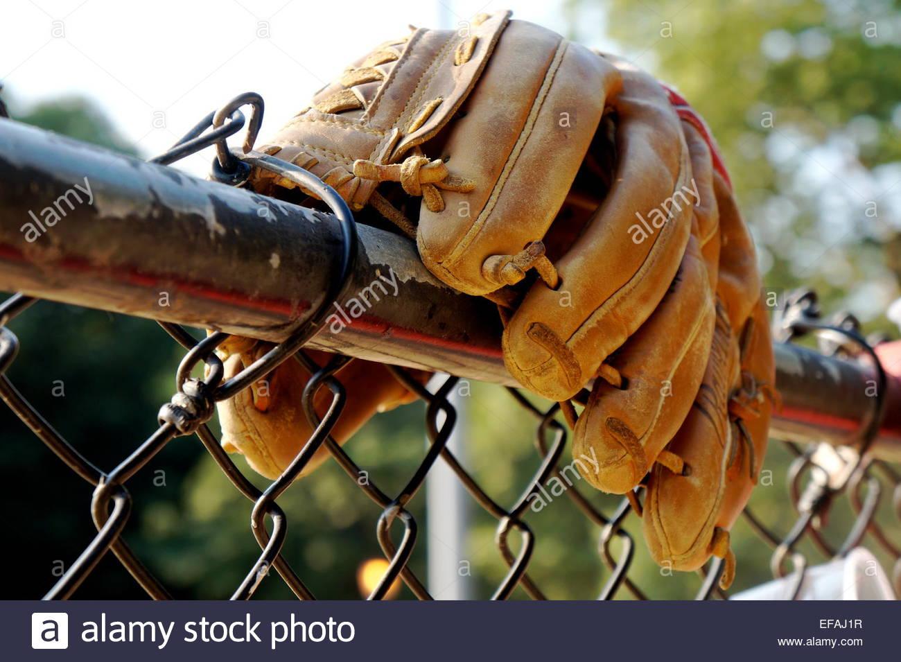 Baseball-Handschuh auf der oberen Leiste der Maschendrahtzaun Stockbild