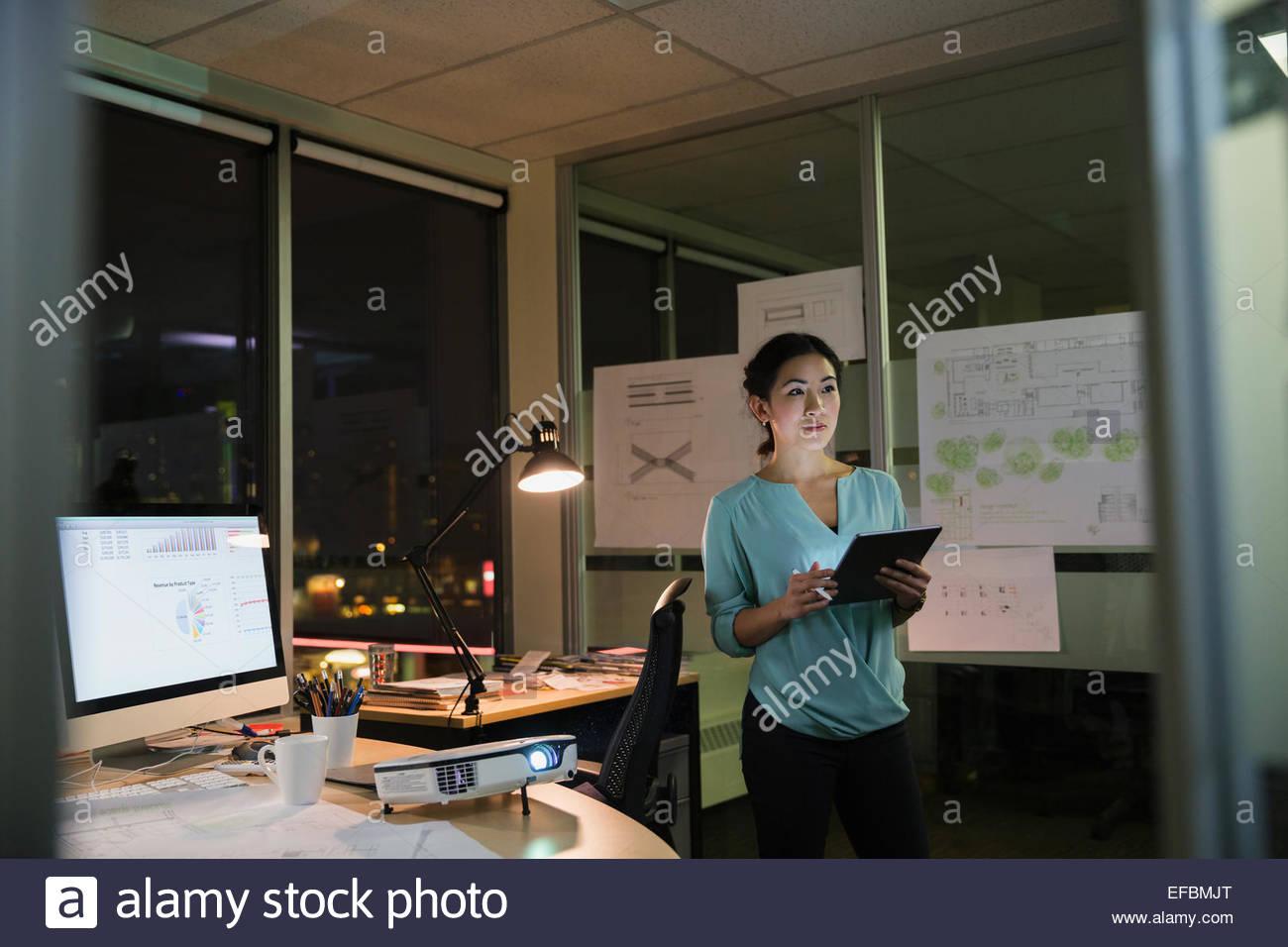 Geschäftsfrau mit digital-Tablette spät im Büro arbeiten Stockbild
