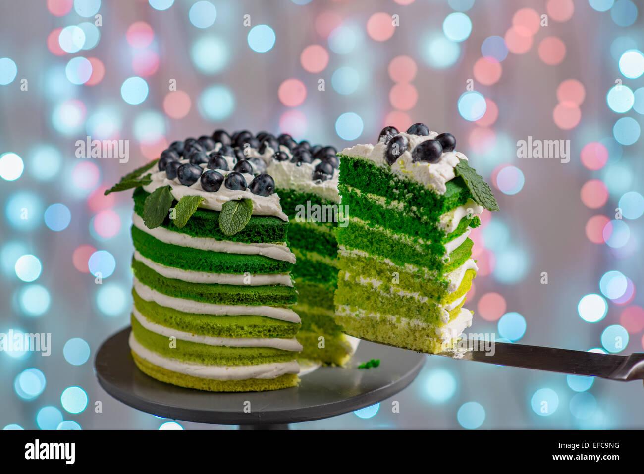Schöne grüne Biskuit schneiden auf festlichen Hintergrund mit Bokeh Licht Stockbild
