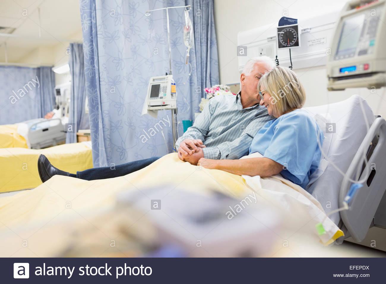 Mann, die Frau im Krankenhausbett beruhigend Stockfoto