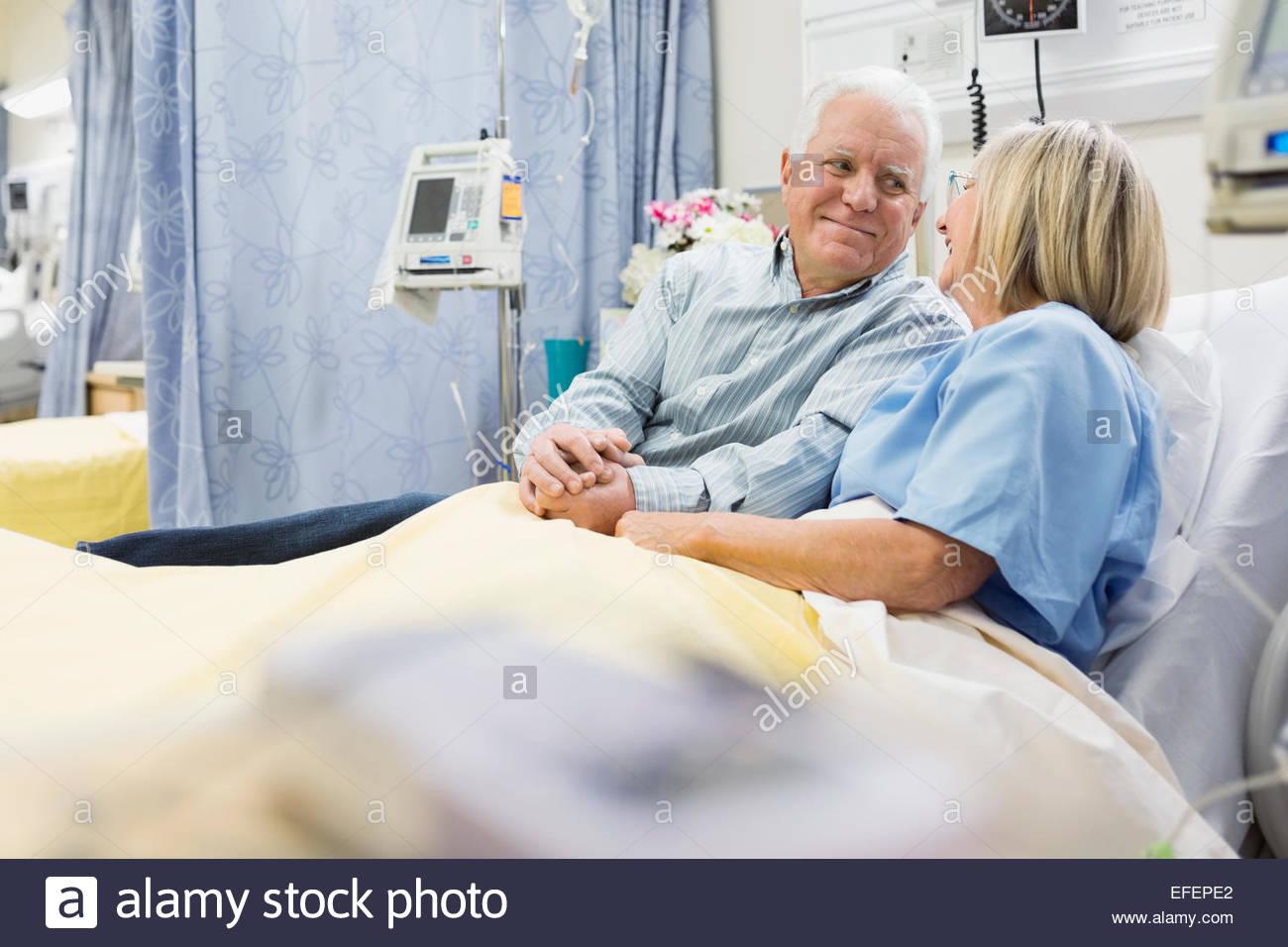Mann und Frau, die Hand in Hand im Krankenhausbett Stockbild