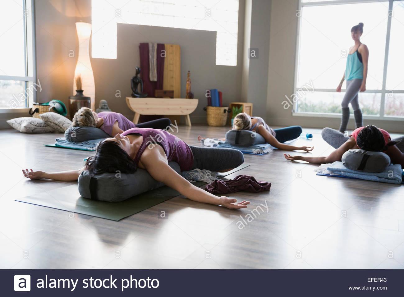 Lehrer beobachten Frauen üben Restoratives Yoga Studio Stockbild