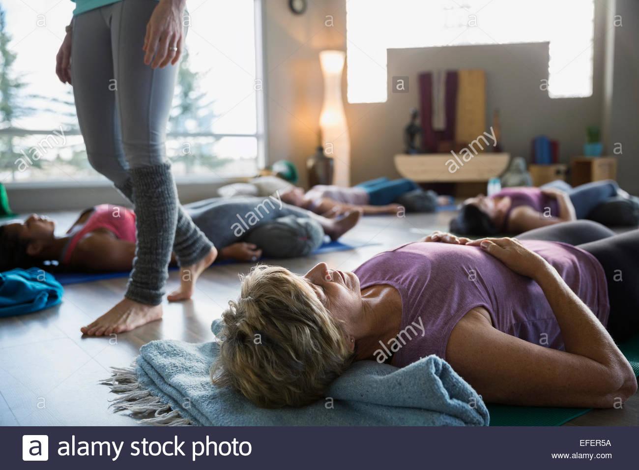 Frauen legen unterstützt Leiche Pose in Restoratives yoga Stockbild
