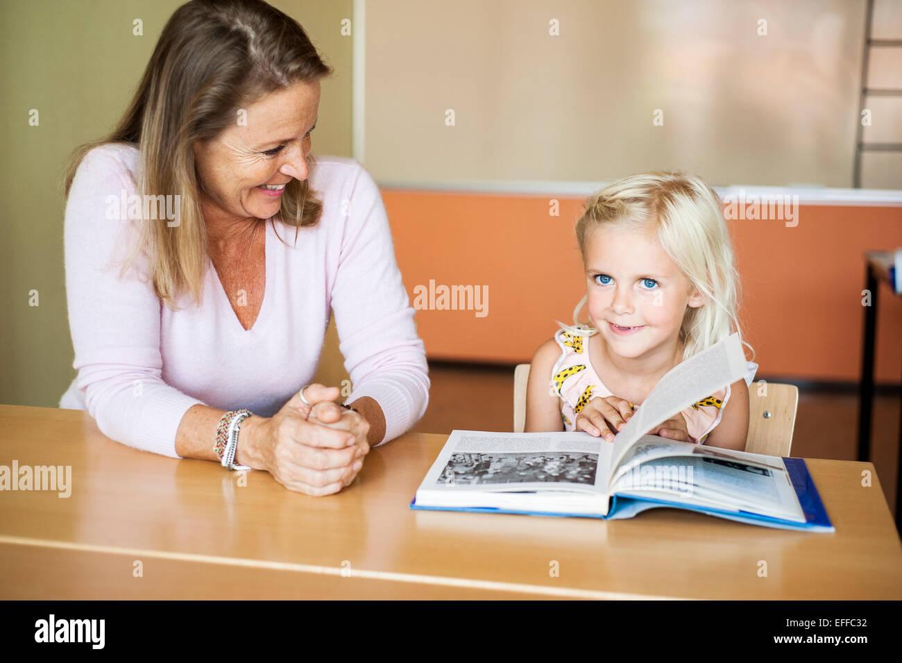 Glückliche Lehrer betrachten Mädchen drehen Buchseite im Klassenzimmer Stockbild