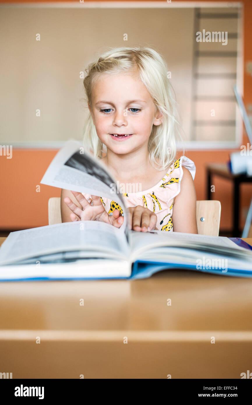 Niedliche Mädchen drehen Buchseite im Klassenzimmer Stockbild