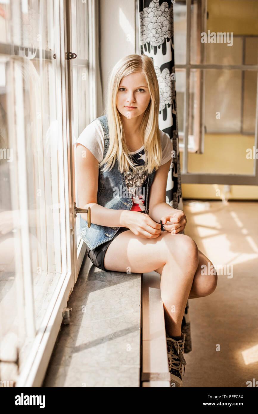 In voller Länge Portrait von Mädchen sitzen auf der Fensterbank in der Schule Stockbild