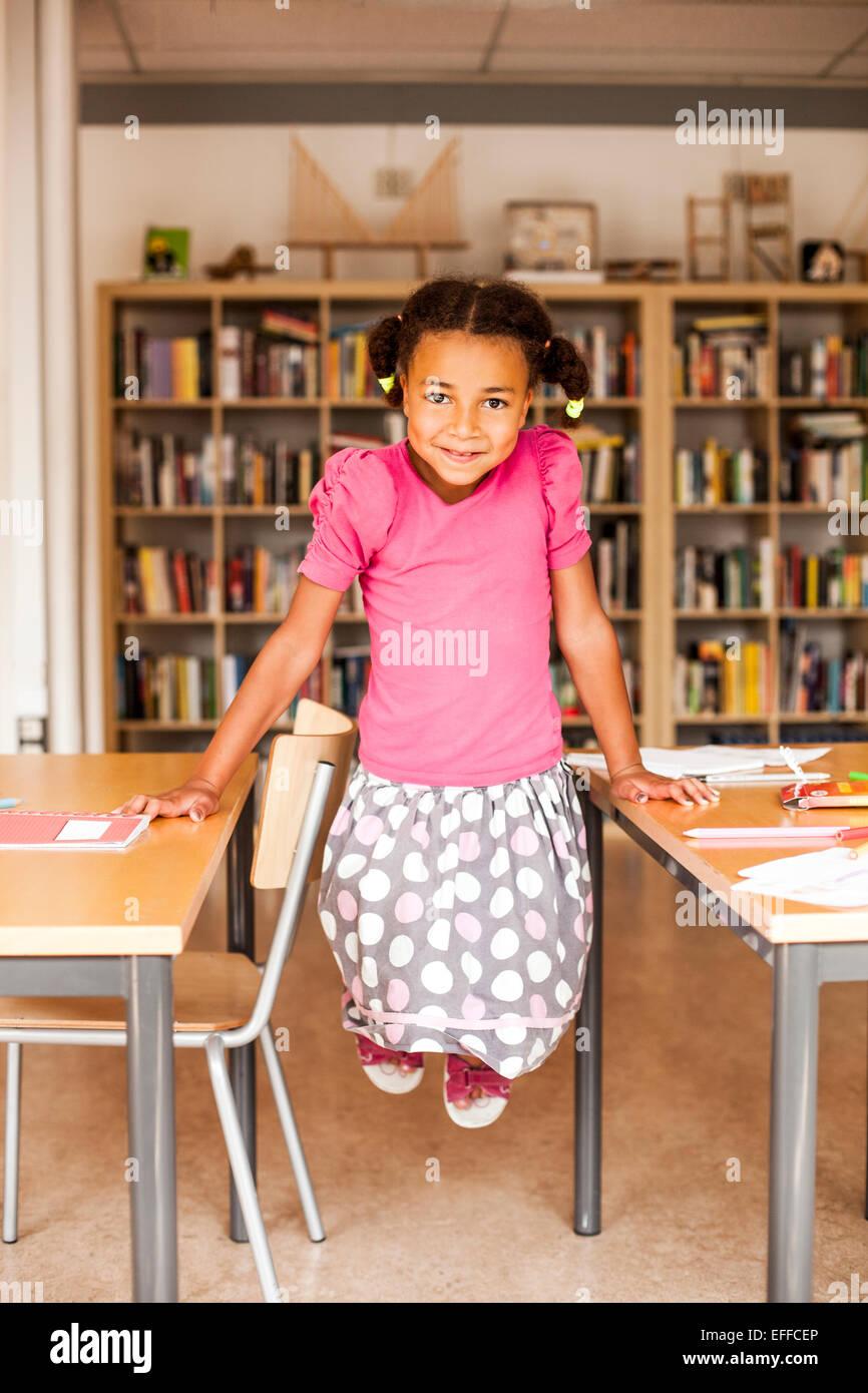 In voller Länge Portrait von verspielten Mädchen im Klassenzimmer Stockbild