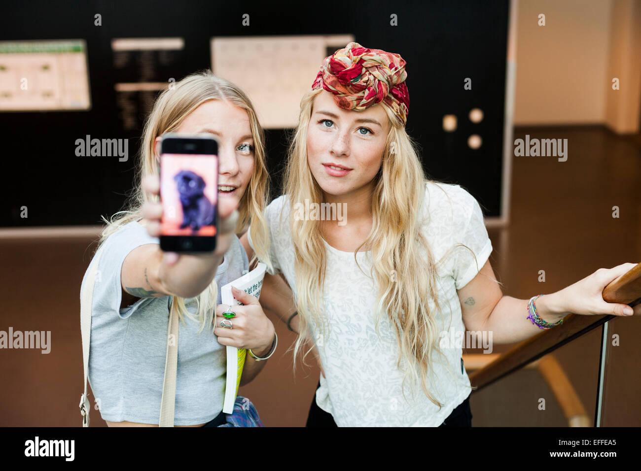 Porträt der Studentinnen mit Foto im Smartphone am college Stockbild