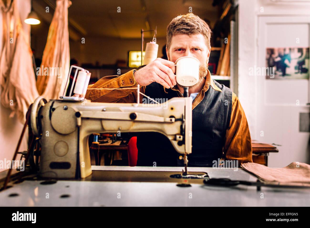 Porträt des Arbeitnehmers Kaffeetrinken beim Sitzen am Nähmaschine in Werkstatt Stockbild