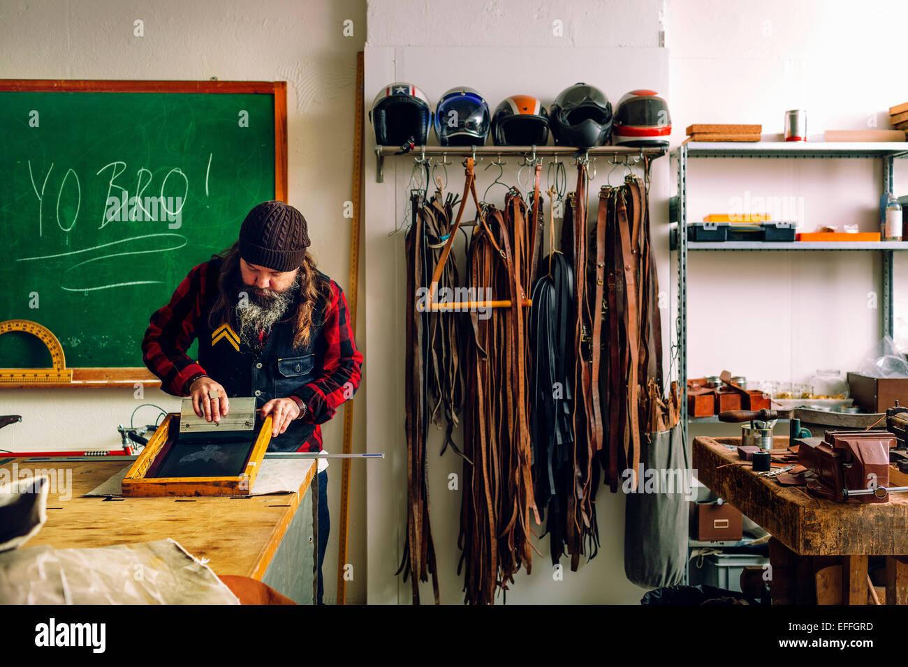 Reifen männlichen Arbeitnehmer mit Rakel zu ziehen Tinte über Schablone auf dem Bildschirm in Werkstatt Stockbild