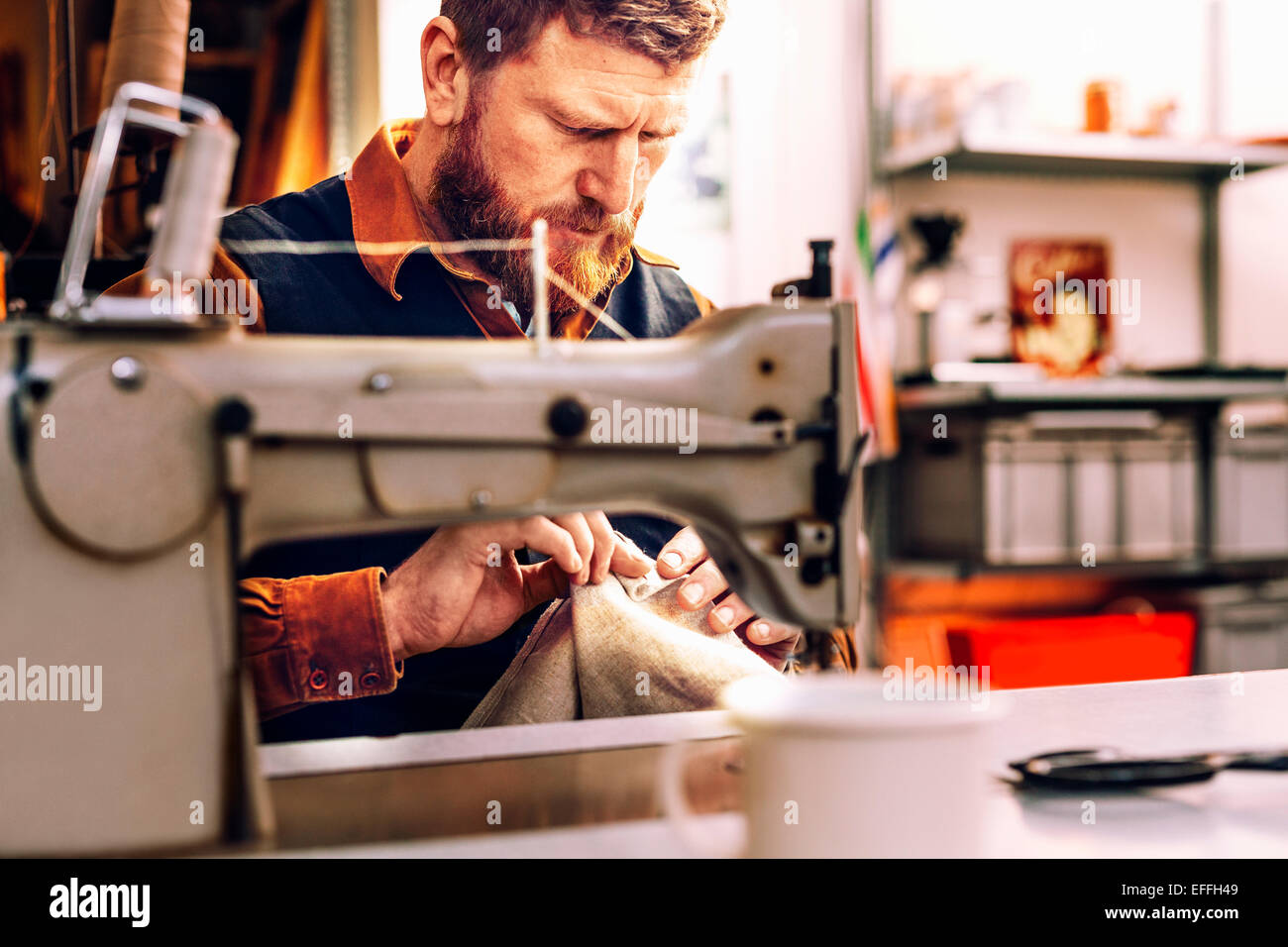 Arbeiter mit Stoff am Nähtisch in Werkstatt Stockbild
