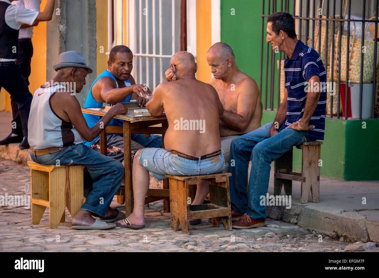 Ältere Kubaner sitzen an einem Tisch auf der Straße spielen Domino, Trinidad, Provinz Sancti Spiritus, Stockbild