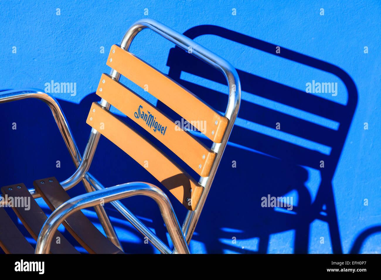 Starke Grafik von San Miguel Marken-Frame Stuhl und Sonneneinstrahlung Gießen Schatten auf blaue Wand Stockbild
