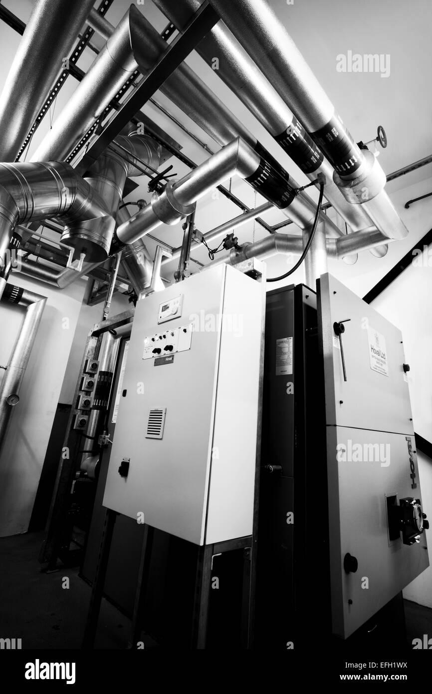 Schwarz-weiß Bild von industriellen Rohrleitungen und Kessel mit ...