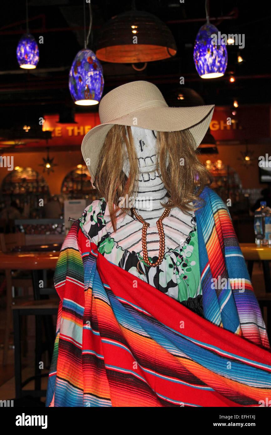 Skelett, die Feiern zum Dia De Los Muertos eingewickelt In bunt gestreifte Decke In einer Tequila-Bar, Miami Flughafen Stockbild