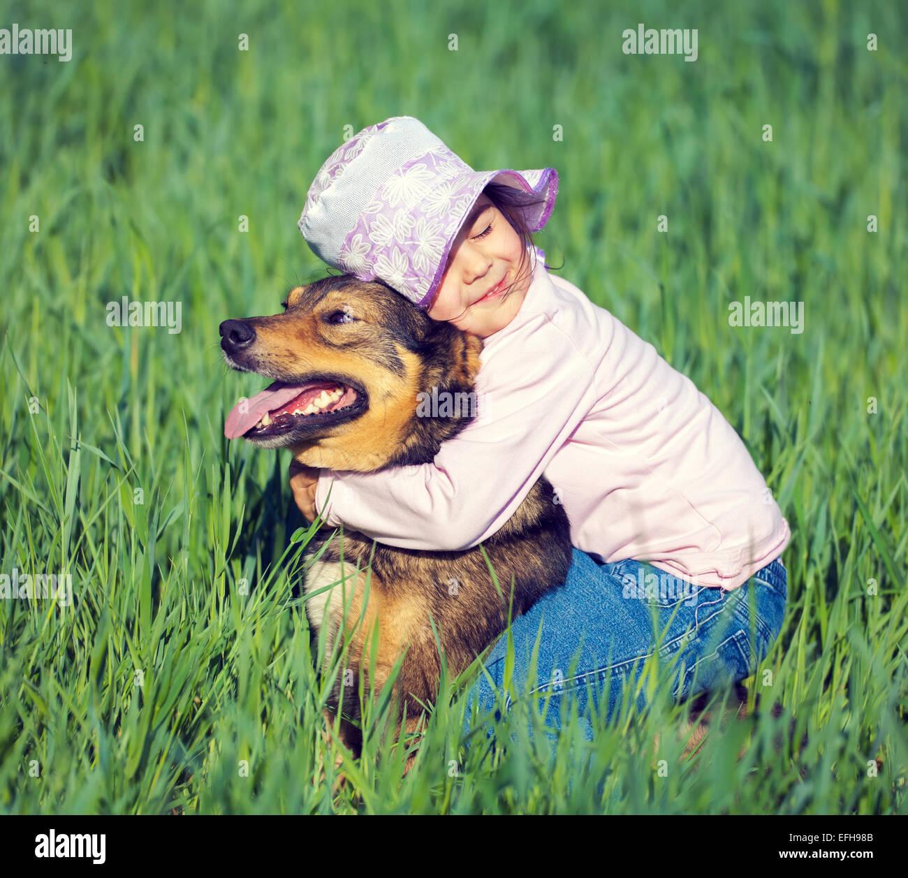 Beste Freunde. Glückliche kleine Mädchen umarmt Hund, sitzen auf dem ...