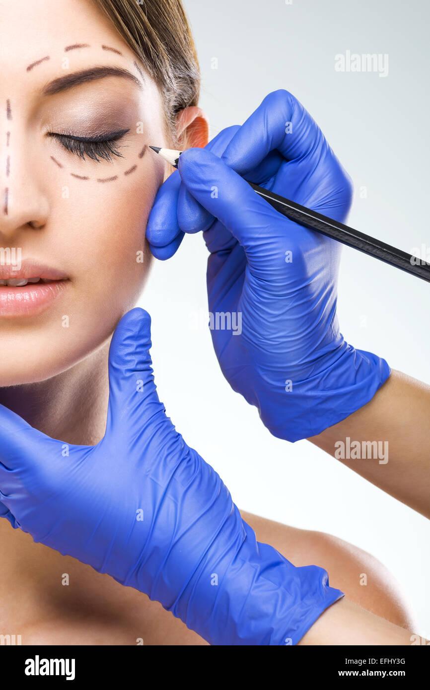 Schöne Frau halbe Gesicht Foto plastische Chirurgie, plastischer Chirurg Hände Stockbild