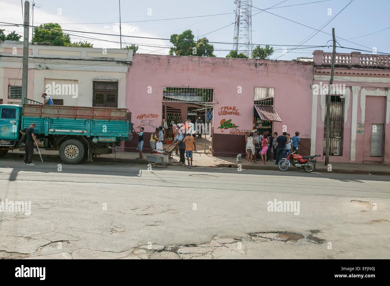 Kubanische Männer entladen frische Produkte aus einem Lieferwagen vor einem Markt mit vielen Kubaner Einkaufen Stockbild